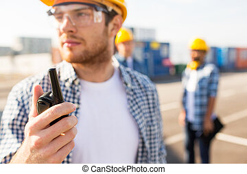 close up of builder in hardhat with walkie talkie -...