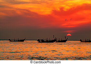 silhouette of fishermen boats fishing in sunset at the beach.