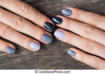 Beautiful hands with the miniature painted in a gray-colored...