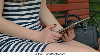 Young female in park using tablet pc communicate via...