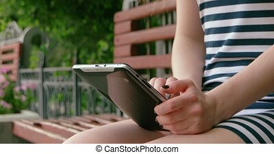 Young girl with digital tablet in a park on bench using internet