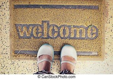 Selfie of foot with welcome doormat