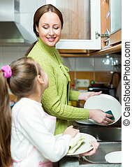 girl with mother washing dishes - Small girl with young...
