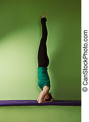 Headstand - Yoga woman exercising headstand on a bench at...