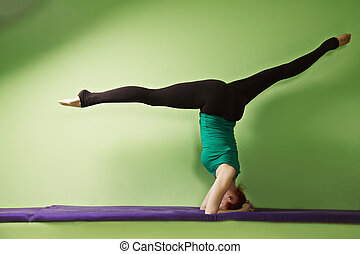 Headstand with legs split - Yoga woman exercising headstand...