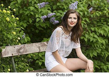 casual woman in luxuriant garden - smiling brunette girl...