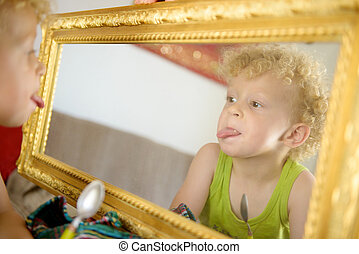 a little child sticking his tongue in the mirror