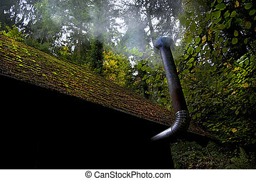 a smoky stovepipe and a mossy roof of a log cabin