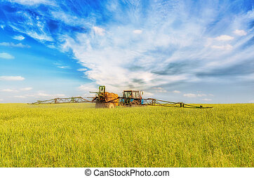 Farming tractor spraying green field beneath blue sky with...