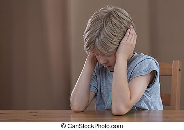 Depressed boy plugging ears - Image of depressed young boy...