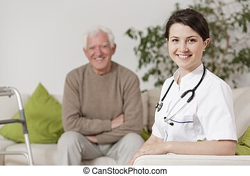 Smiling doctor during home visit - Image of smiling doctor...