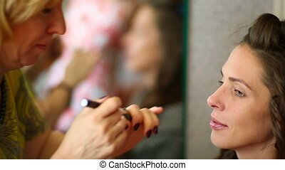 Make-up - Makeup artist apply the cream on the eyelids model...