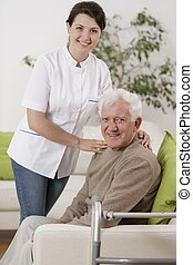 Young physiotherapist supporting senior patient