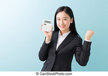 electronic calculator - young attractive asian businesswoman...