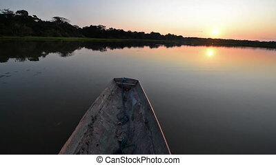 Canoe on a Lake at Sunset - Canoe moving on a lake in the...
