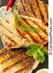 Grilled carp fillets on cutting board