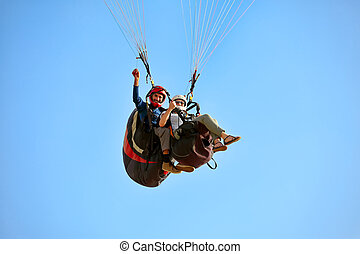 paragliding in the mediterranean sky - A man and woman...