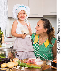 Mother with daughter cooking - Happy woman with little girl...