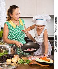 Mother with daughter cooking - Happy woman with little...