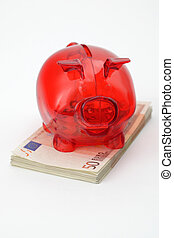 Piggy bank standing on top of Euro banknotes