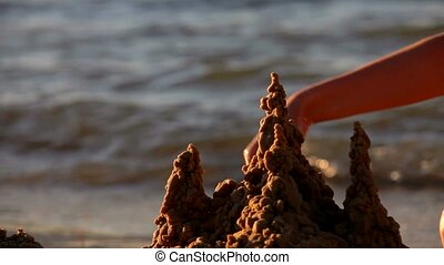 Girl on the Sea Builds a Sand Castle - On the sandy beach. A...