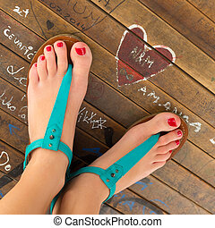 Female feet wearing turquoise sandals. - Graphical image of...