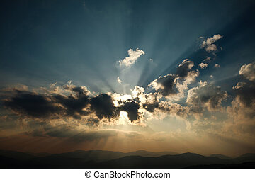 Shining sunrise over the mountains in a cloudy sky, nature background