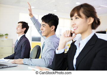 business man raising hand  in conference room