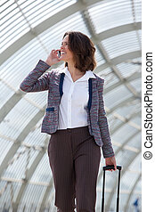 Business woman walking and talking on mobile phone -...