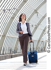 Smiling business woman traveling with bag - Full length...