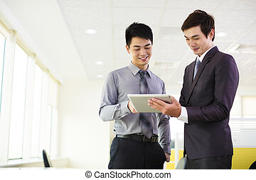 business partners looking at tablet and discussing