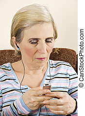 Senior woman listening music - Senior women holding an mp 3...