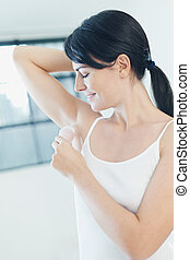 stick deodorant - woman putting on stick deodorant and...