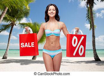 happy woman in bikini with shopping bags on beach - people,...