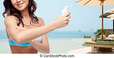 happy young woman in swimsuit applying sunscreen - people,...