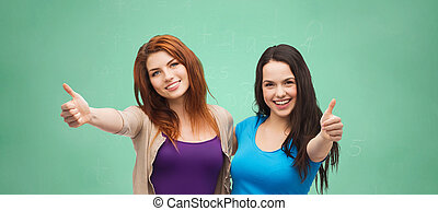 happy student girls showing thumbs up over green
