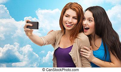 happy teenage girls taking selfie with smartphone -...