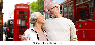 happy senior couple on london street in england - family,...