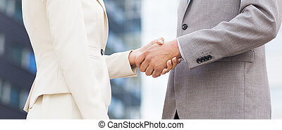 close up of business couple shaking hands