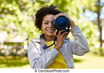 happy african woman with digital camera in park - people,...