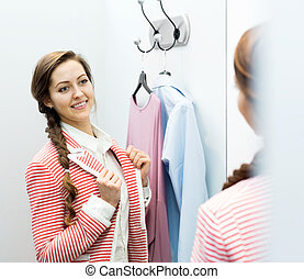 woman in the dressing room - smiling young female with new...