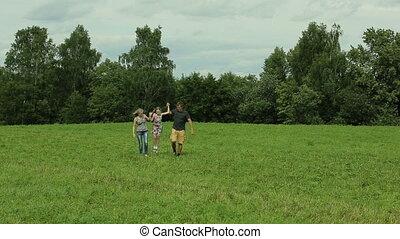 Happy family walking on green meadow