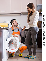 Woman showing broken washing machine - Young woman showing...