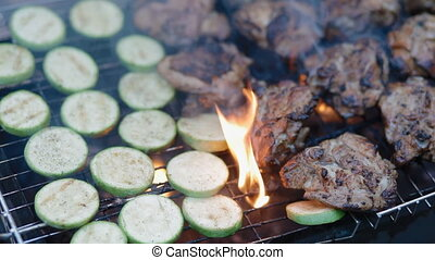 Squash and meat on the grill with smoke and fire. Food for...