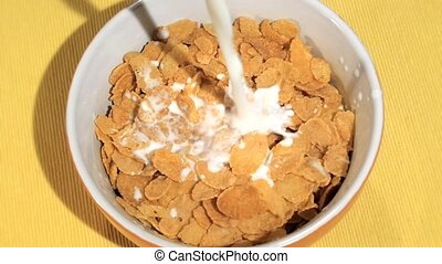 breakfast time, cornflakes and milk - cornflakes pouring...