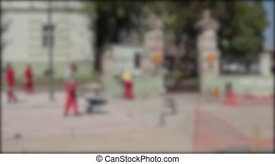 Masons are fitting flagstone. - Blurred view on construction...