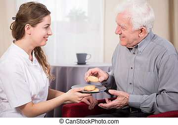 Free time in sanitarium - Pensioner and his nurse during...