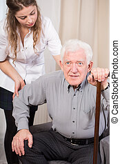 Senior trying to get up - Elder man trying to get up with...