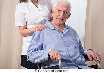Elder man in a wheelchair - Pensioner dressed in pyjama and...