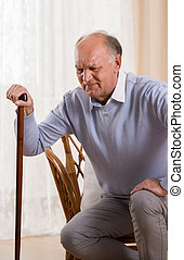 Trying to stand up - Older man with walking stick trying to...